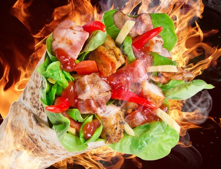 Chicken slices in a Tortilla Wrap with fire flames  photo