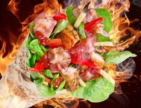 tortilla wrap: Rodajas de pollo en una envoltura de tortilla con llamas de fuego