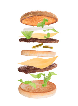 Delicious hamburger with flying ingredients on white  photo
