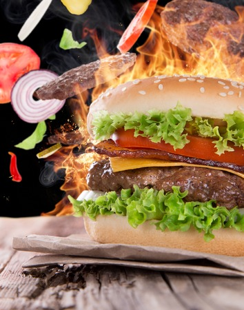 Delicious hamburger with fire flames on wooden  photo