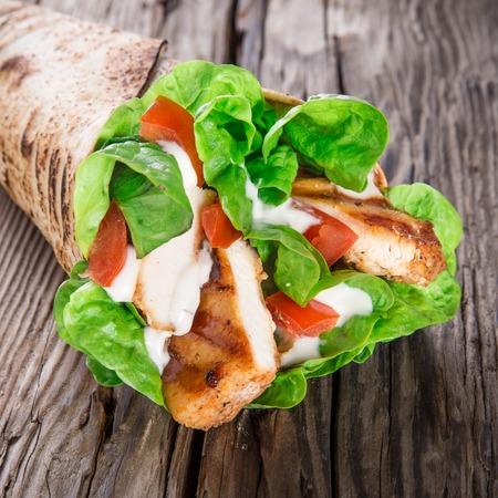 tortilla wrap: Tiras de pollo en una envoltura de tortilla con lechuga en la madera Foto de archivo