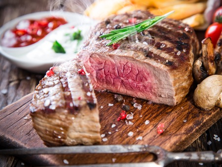 mignon: Delicious beef steak on wooden table, close-up