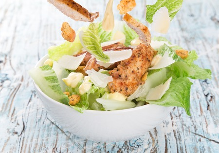 Caesar salad with chicken and greens on wooden table photo