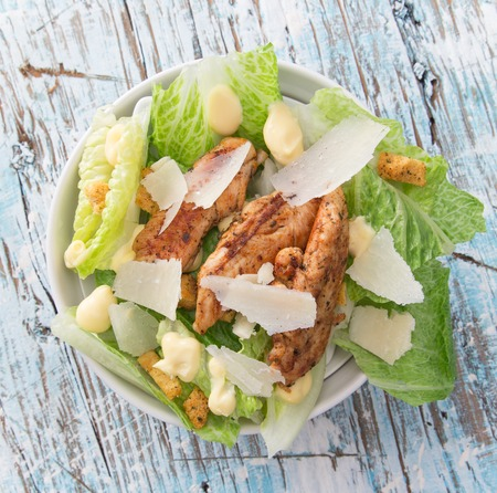 CHICKEN CAESAR SALAD: Caesar salad with chicken and greens on wooden table