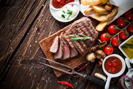 parrillero: Filete de carne sabrosa en la mesa de madera. Foto de archivo