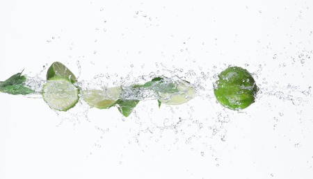 splash de agua: limas frescas con salpicaduras de agua. Foto de archivo