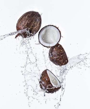 Fresh coconuts with water splash on white background.