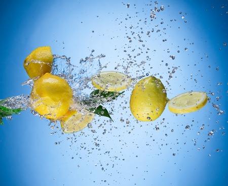 splash de agua: limones frescos sobre fondo azul.