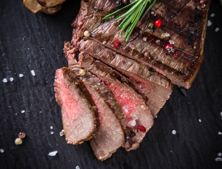 fillets: Tasty beef steak on stone desk. Stock Photo