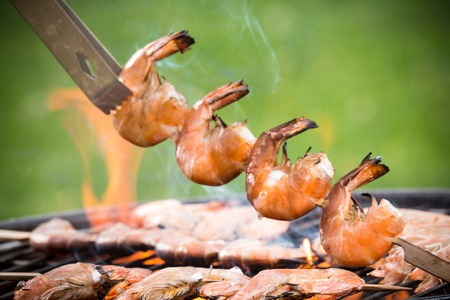 Delicious prawn on grill with flames in background photo