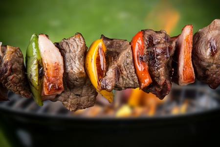 barbecue fire: Tasty skewers on black background, close-up  Stock Photo