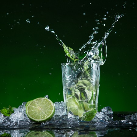 Fresh mojito cocktail in freeze motion splashing, close-up