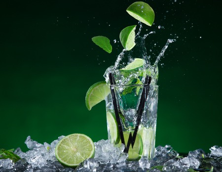 Fresh mojito cocktail in freeze motion splashing, close-up  photo