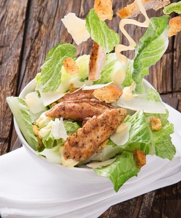 ensalada de verduras: Caesar salad with flying ingredients.