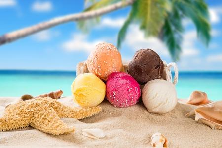 Ice cream scoops on sandy beach, close-up  photo