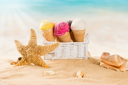 Ice cream scoops on sandy beach, close-up  photo