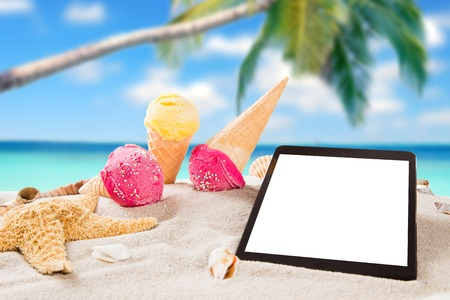 Ice cream with tablet on sandy beach, summer concept  photo