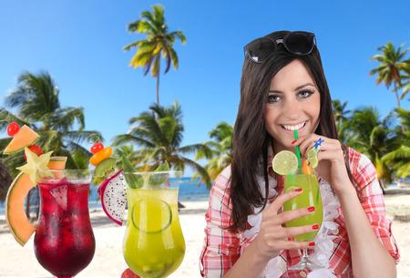 cocteles de frutas: Joven mujer feliz con cócteles de frutas en la playa arenosa
