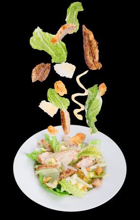 ensalada cesar: Ensalada César con ingredientes en movimiento