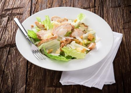 CHICKEN CAESAR SALAD: Tasty caesar salad on wooden table Stock Photo