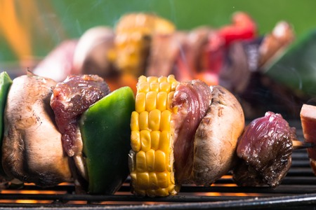 Delicious skewers on grill photo