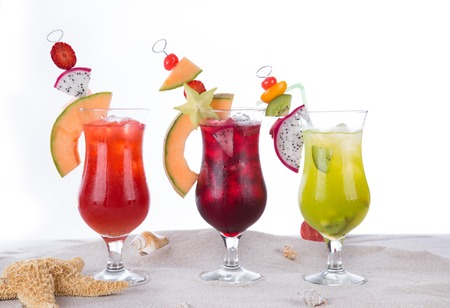 Fruit cocktails on sandy beach isolated on white background