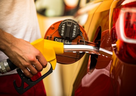 Hand refilling the car with fuel, close-up