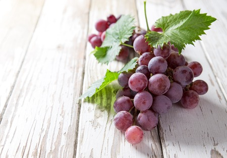 wine and grapes: Grapes on wooden table, close-up.