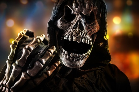 Grim Reaper: Grim reaper on a dark background, halloween background. Stock Photo