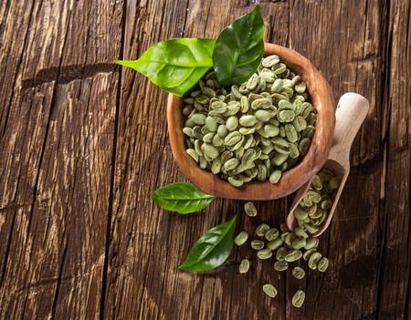 plant antioxidants: green coffee beans in wooden bowl, close-up. Stock Photo