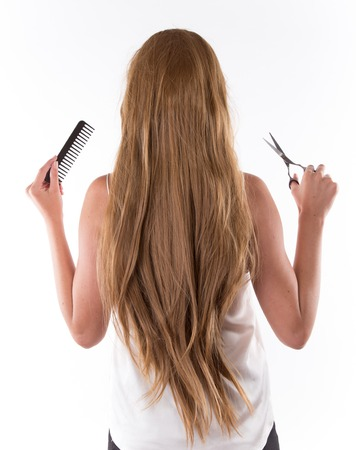 thinning: cutting young beautiful brunette womans hair with scissors