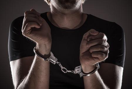 Man handcuffed hands, close-up.