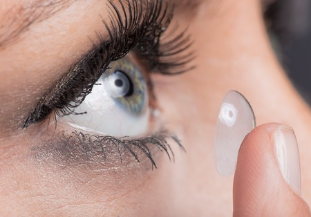 nearsighted: Closeup of a woman inserting a contact lens