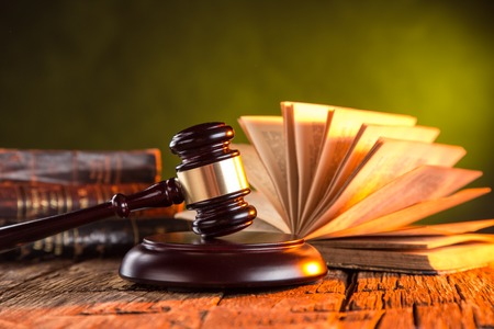 Wooden gavel and books on wooden table, law concept photo