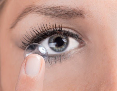 Closeup of a woman inserting a contact lens photo