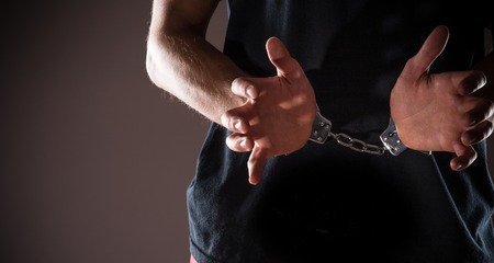 handcuffed hands: Man handcuffed hands, close-up.