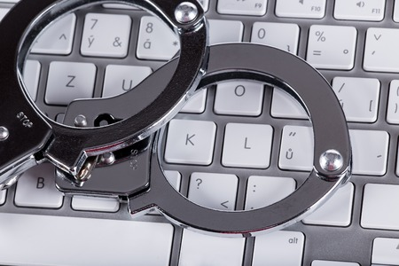 cyber crime: Cyber Crime, computer keyboard and handcuffs Stock Photo