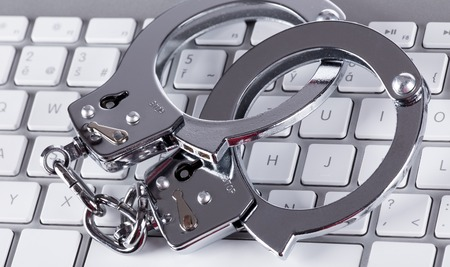 three dimensional accessibility: Cyber Crime, computer keyboard and handcuffs Stock Photo