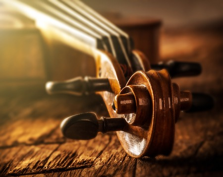 cellos: violin in vintage style on wood background