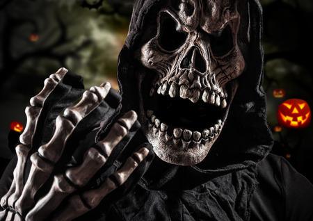 Grim reaper on a dark background, halloween background. Stock Photo