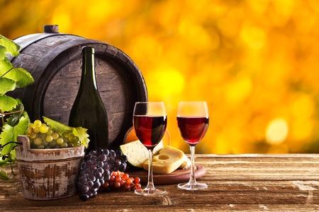 Wein-Stillleben, Glas, junge Reben und Trauben