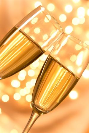 Champagne glasses on light bokeh background photo