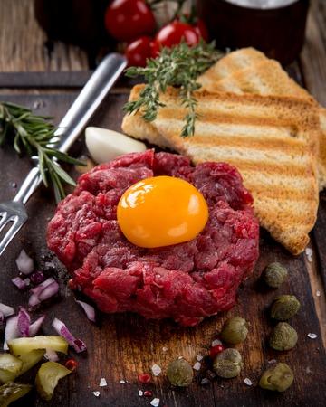 steak tartare: fresh beef tartar with egg, close-up.