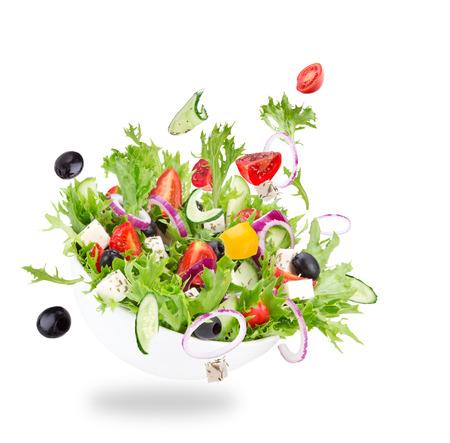 新鮮なサラダ野菜成分を飛んでいる白い背景上に分離。