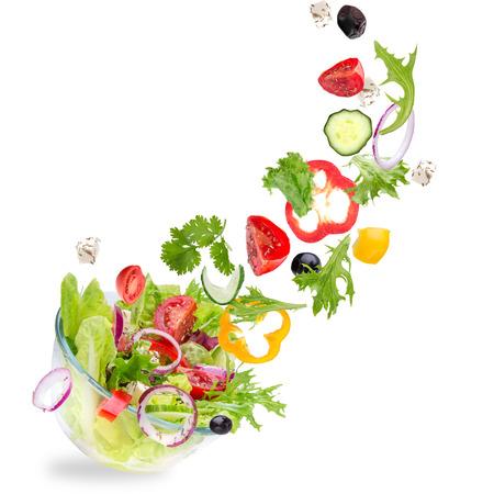 흰색 배경에 격리 된 비행 야채 재료와 신선한 샐러드.