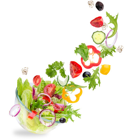 Fresh salad with flying vegetables ingredients isolated on a white background.