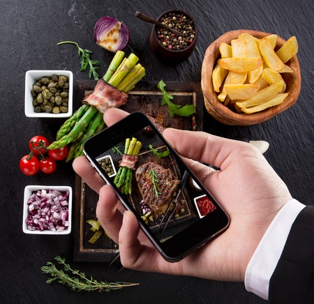 food on table: Hand taking photo of prepared food with smartphone Stock Photo