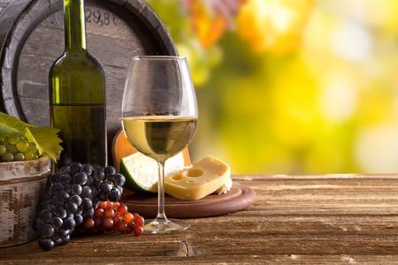 Wijn stilleven, glas, jonge wijnstok en tros druiven Stockfoto