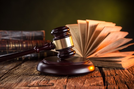 Wooden gavel and books on wooden table, law concept Imagens