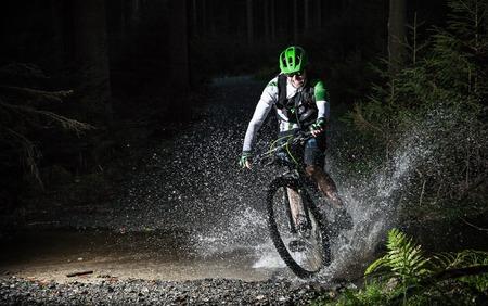 mountain biking: Mountain biker speeding through forest stream. Water splash in freeze motion.